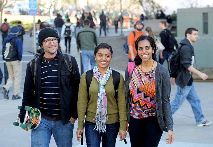 A smiling and diverse group of Berkeley students walking through our campus