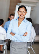 Businesswoman with crossed arms smiling in front of her team at work